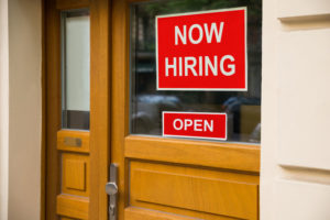 45706235 – the text now hiring sticker attached on glass door of the office